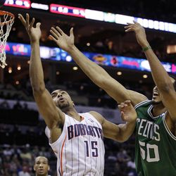 Charlotte Bobcats' Gerald Henderson (15) and Boston Celtics' Ryan Hollins (50) battle for a rebound during the first half of an NBA basketball game in Charlotte, N.C., Sunday, April 15, 2012.