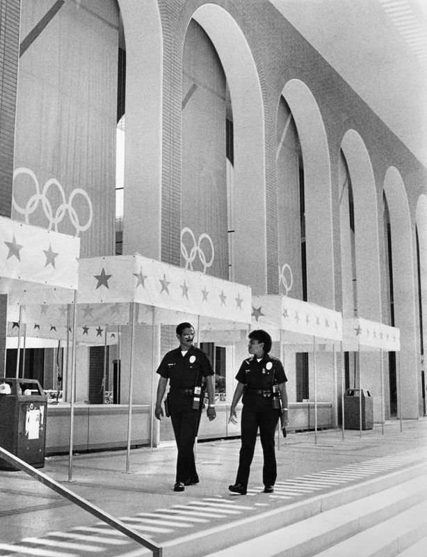Black and white photo from 1984. Two police officers patrol the Olympic Village at USC, adorned with banners with prints of stars and the Olympic rings.