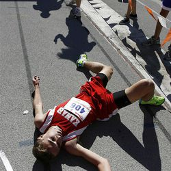 Yanni Gallagher of Kanab falls to the ground after lunging at the finish line to take first place in the boys 2A state cross country high school competition at Sugarhouse Park in Salt Lake City, Wednesday, Oct. 19, 2011.