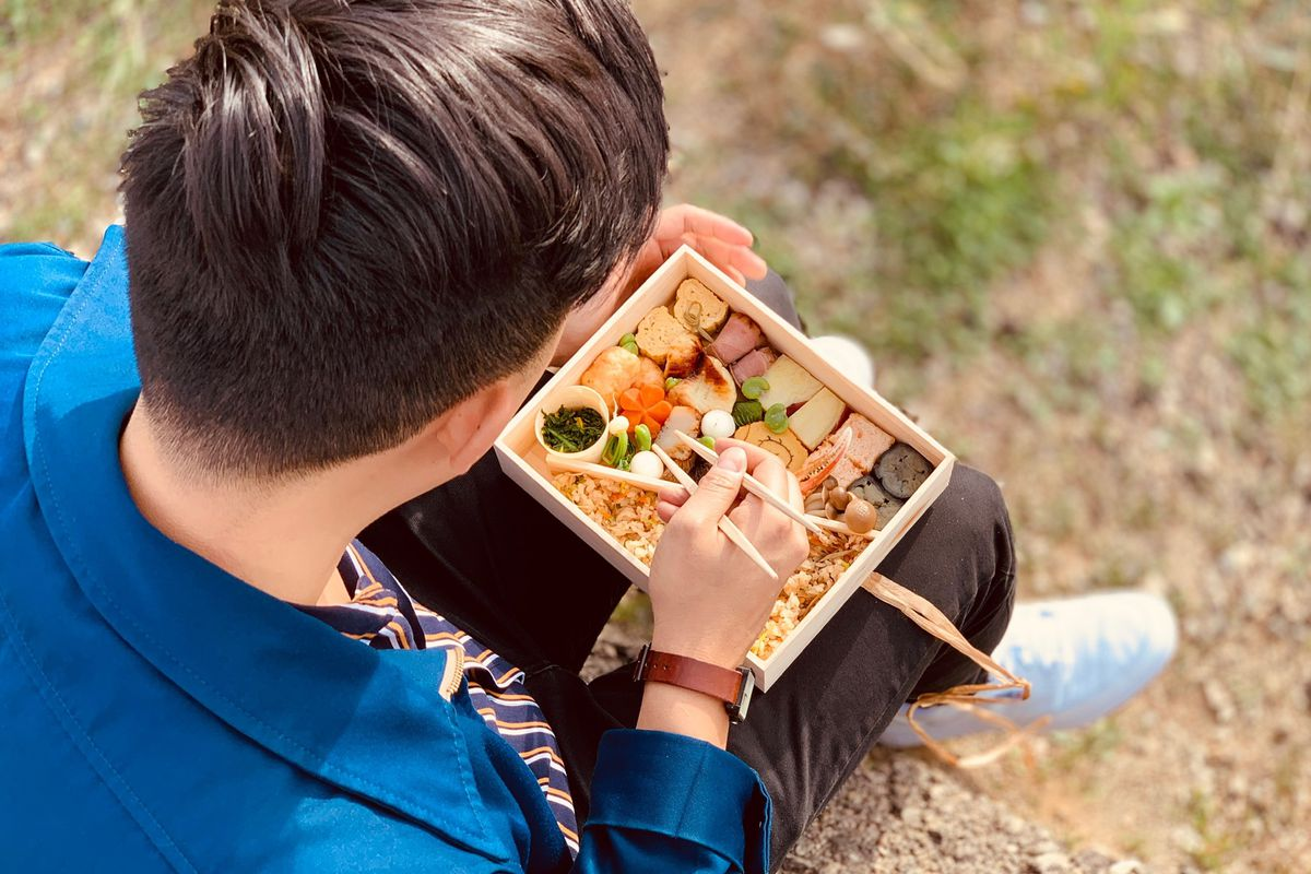 Man sitting outdoors with a bento box in his lap.