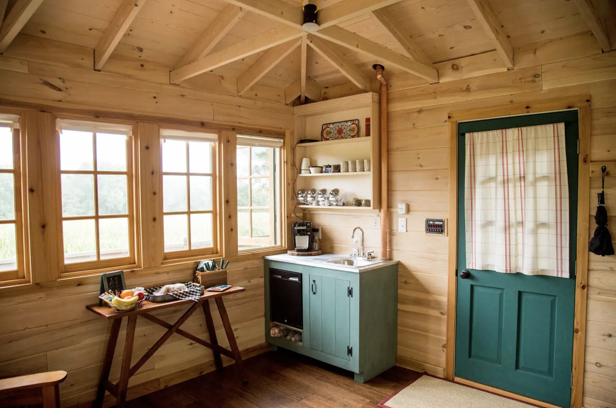A wooded cabin with a small kitchen area, a blue door, and table with coffee, fruit and muffins.
