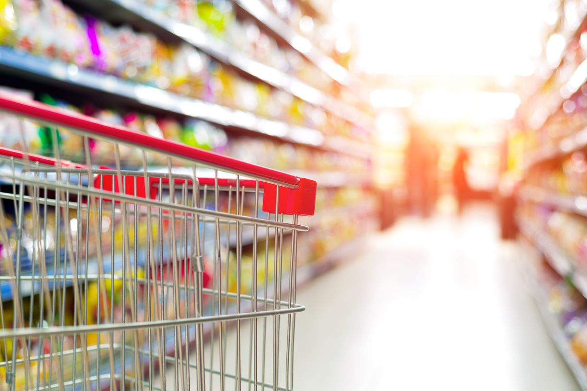A shopping cart in the foreground, with grocery store aisles blurry in the background