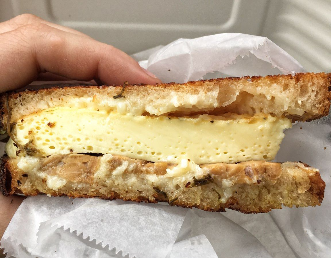 A side view of a farm egg sandwich held in someones hand with eggs, tempeh, cheese, and crisp, buttery bread.