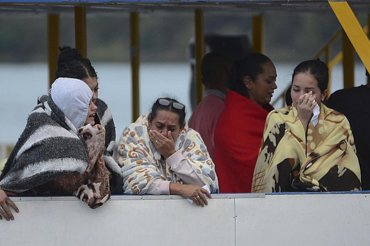 People who survived a sunken ferry, cry as they wait for more information about their missing friends and relatives, at a reservoir in Guatape, Colombia, Sunday, June 25, 2017. Nine people were dead and 28 missing after a tourist ferry packed with around