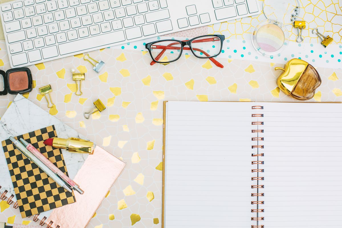 An open notebook, glasses, a keyboard, and other office supplies on a desk.