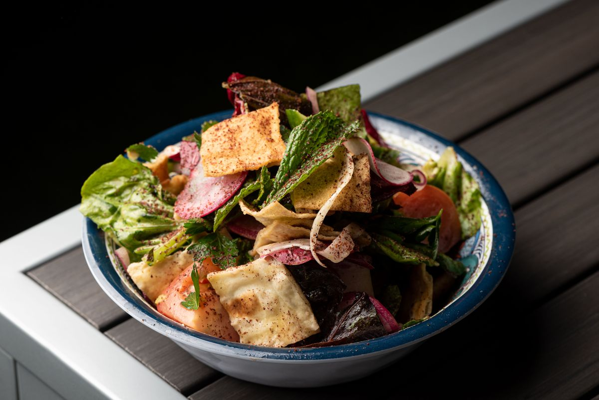 A green salad with crispy pita bites in a bowl on a table.