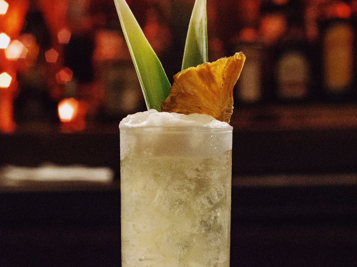 A tall cocktail on a bar, with two pineapple fronds and a pineapple wedge sticking out the top. The cocktail is a milky yellow with a foamy head. The bar is lit by neon