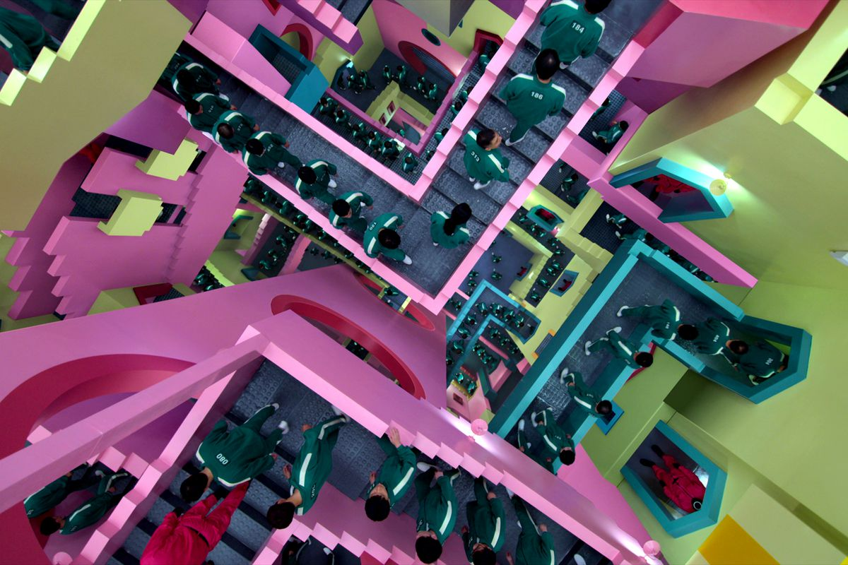 A vivid neon pink and green maze full of people, seen from the top down, in Squid Game