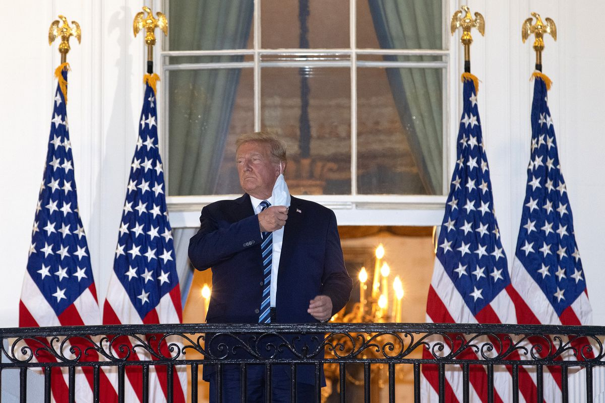 Trump stands on the White House balcony removing his mask.
