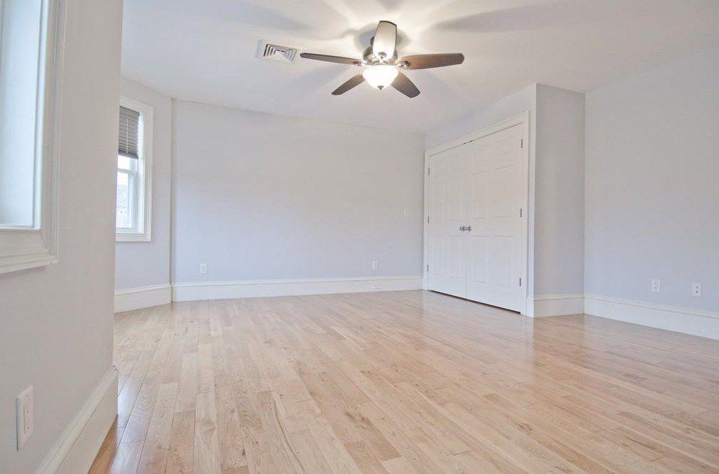 An empty bedroom with a ceiling fan.