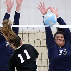 West Jordan's Makena Myers hits the ball as Woods Cross' Lauren Bodily and Annie Lewis attempt a block during a high school volleyball game at West Jordan High School in West Jordan on Thursday, Sept. 2, 2021.