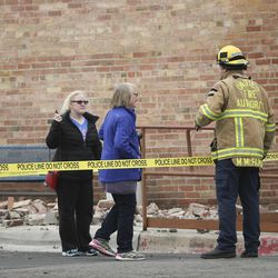 A first responder talks with concerned neighbors in Magna after a 5.7 earthquake hit early Wednesday, March 18, 2020.