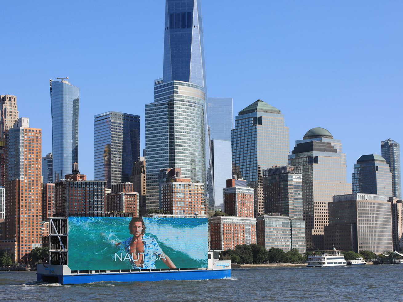 A billboard floats on a boat in the Hudson River, with the New York City skyline behind it.