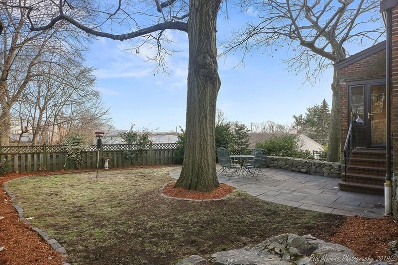 A backyard with a stone patio behind a house, and there's a lone oak tree in the yard.