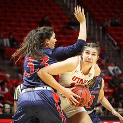 Utah Utes forward Emily Potter (12) ducks under the arm of Saint Mary's center Claire Ferguson (33) to take a shot from the key as Utah hosts Saint Mary's at the Huntsman Center in Salt Lake on Saturday, Dec. 2, 2017.