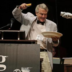 CORRECTS TO REMOVE REFERENCE TO KIRSHER WINNING 2011 NOBEL PRIZE FOR PHYSICS, ADDS HIS CURRENT TITLE - Harvard University Clowes Professor of Science Robert Kirshner holds up a piece of pie while explaining a pie chart about the universe, shortly before eating it, during a performance at the Ig Nobel Prize ceremony at Harvard University, in Cambridge, Mass., Thursday, Sept. 20, 2012. The Ig Nobel prize is an award handed out by the Annals of Improbable Research magazine for silly sounding scientific discoveries that often have surprisingly practical applications.