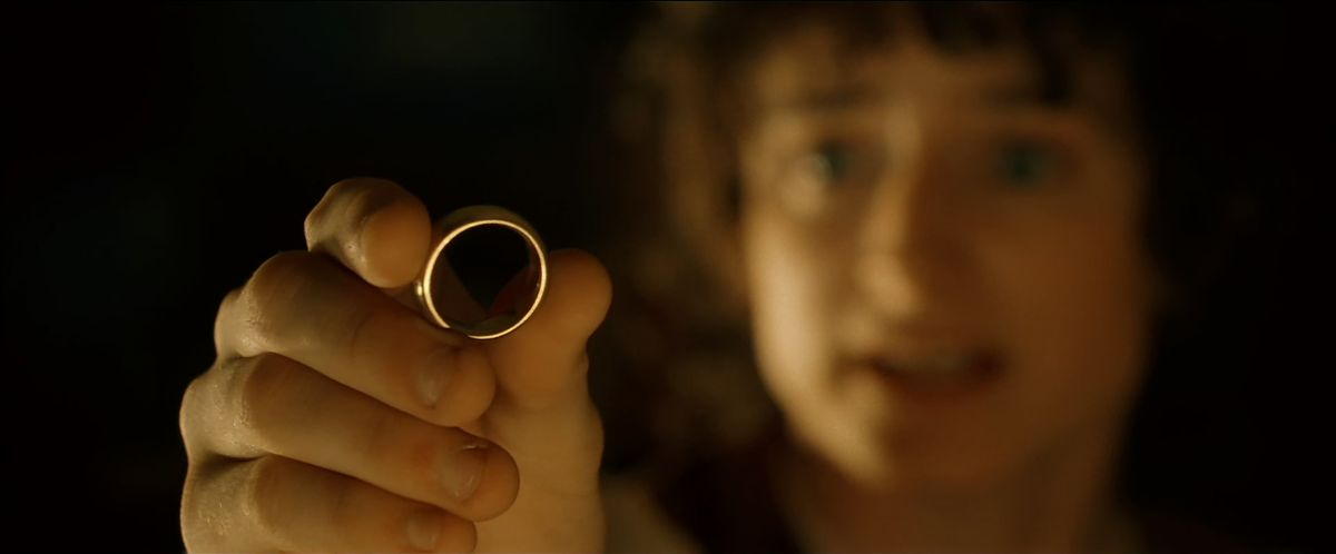 Frodo (out of focus) holds out the One Ring (in focus) with a pleading gesture in The Fellowship of the Ring.