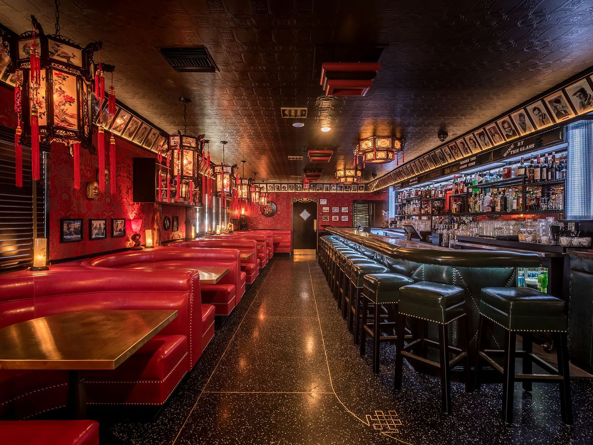 A dim red and black interior of a redone restaurant with lots of throwback touches and a tiki vibe.
