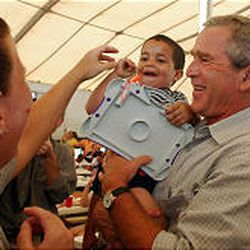 President Bush holds DaQuan J'Ray Williams, 3, during a tour Monday of the Church of God in Gulfport, Miss.