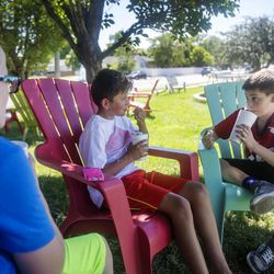 Boston Ungricht, 11, Isaac Wright, 12, and Nathan Keddington, 11, eat snow cones in the shade at the Sno Shack in Sugar House in Salt Lake City on June 19, 2017.