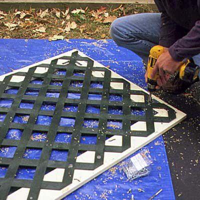 Man Drills Clearance Holes In Lattice Panels
