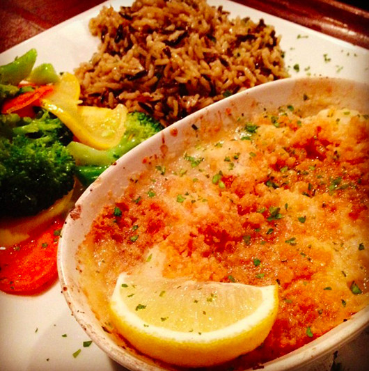 Closeup on a breadcrumb-topped baked fish dish with a wedge of lemon, rice, and steamed vegetables