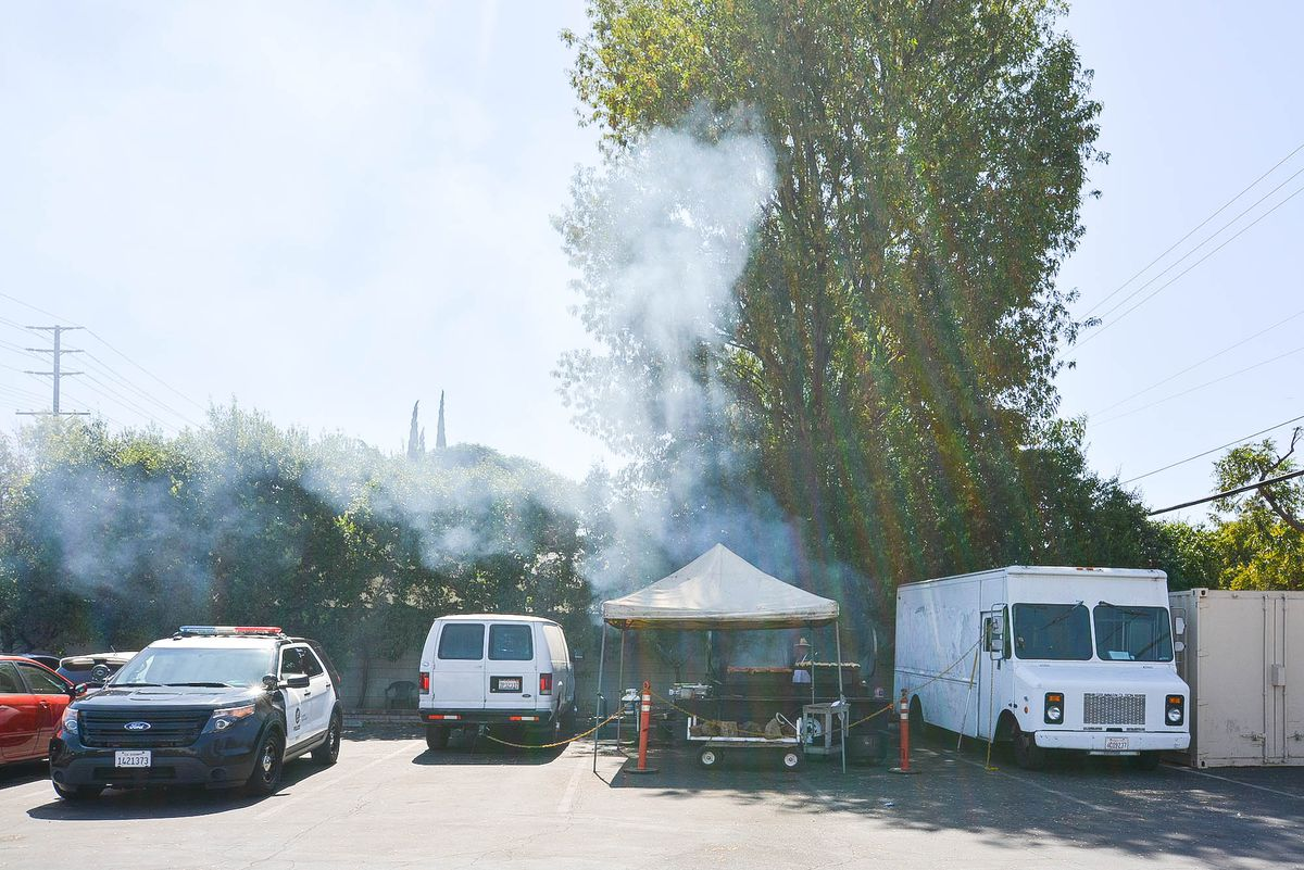 Smoke rolls from beneath a barbecue tent in a parking lot.