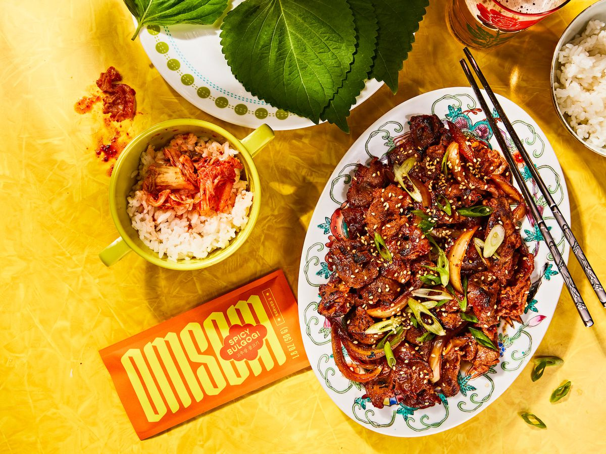An oval plate with brownish meat with a pair of chopsticks next to it. An orange spice packet sits next to them