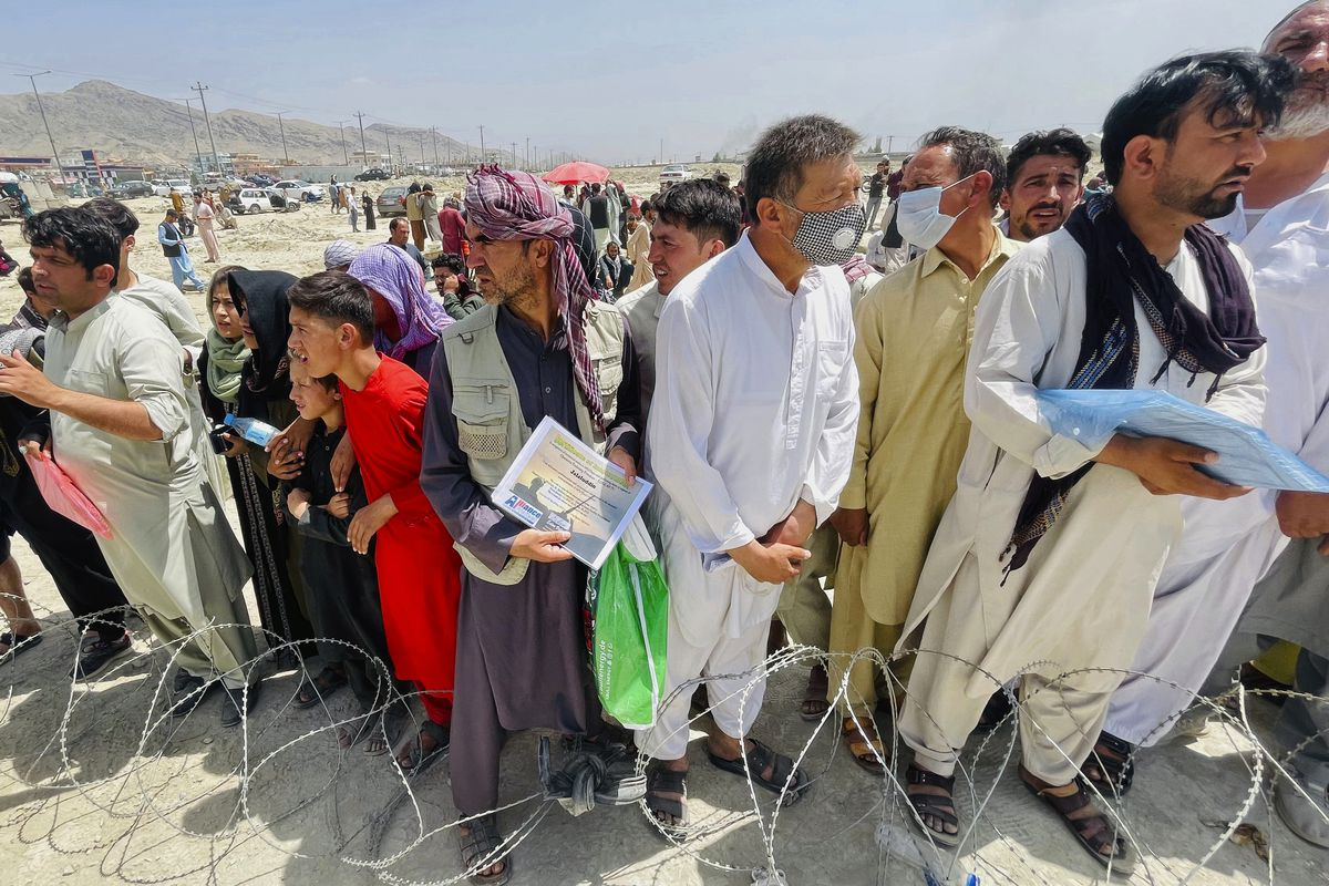A man holds a certificate acknowledging his work for Americans as people gather outside the airport in Kabul, Afghanistan