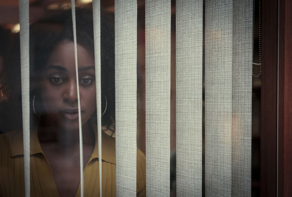 Simona Brown stares through the window blinds in Netflix's Behind Her Eyes