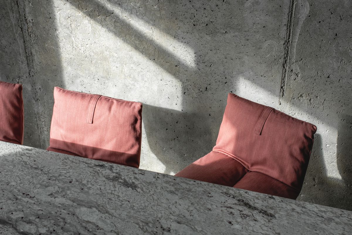 Close up shot of pink bar stools, with a backdrop of concrete walls.