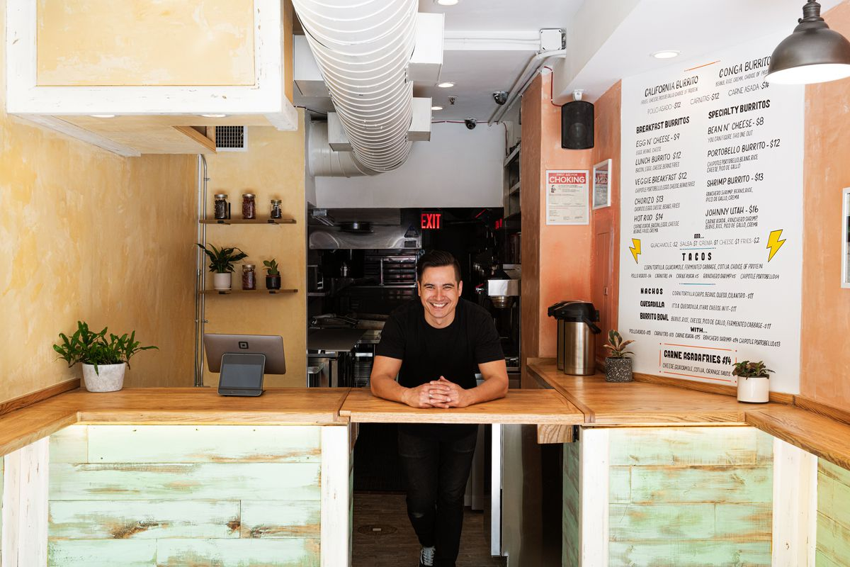 A man in a black shirt and pants is standing behind the counter of a restaurant, whose menu advertises tacos, burritos, and carne asada fries