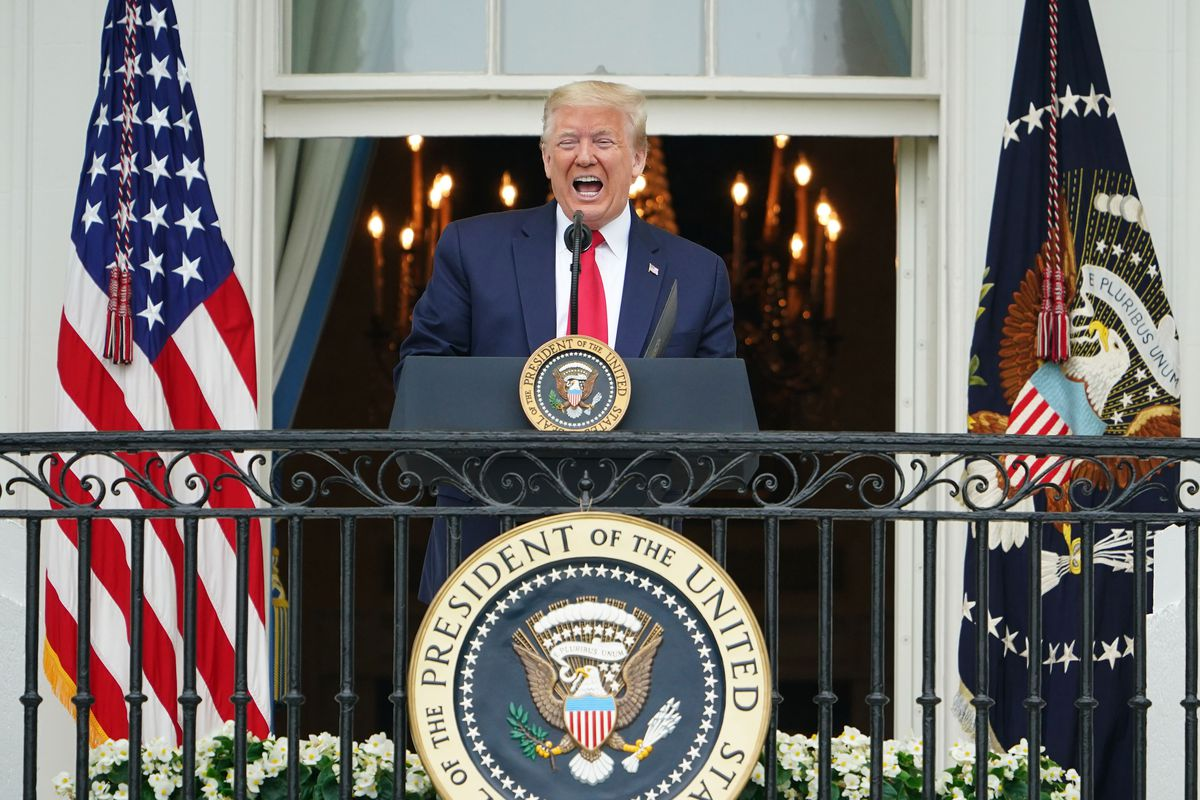 Trump stands on a wrought iron balcony, the seal of the president before him, flanked by flags. He speaks emphatically in a dark suit and red tie.