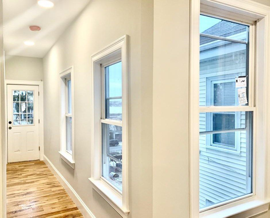 A hallway in a renovated apartment, with windows.