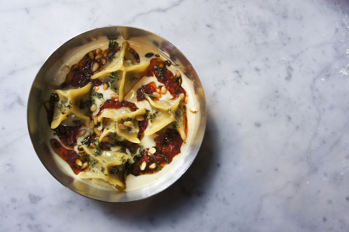 Beef and sour cherry manti in a metal dish