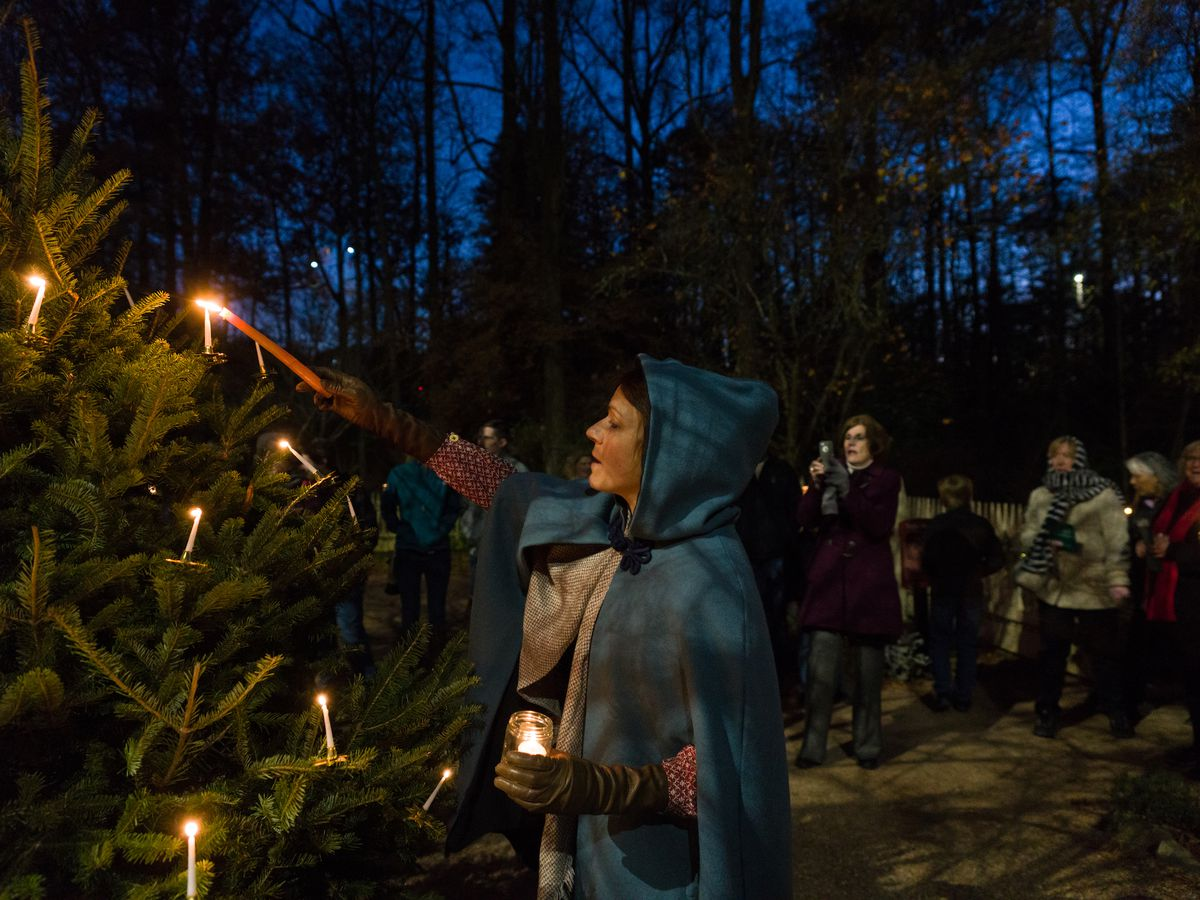 Woman in period costume lighting candles on a Christmas tree.