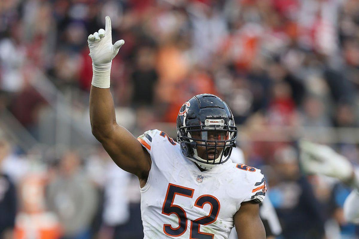 Khalil Mack, in a white Bears uniform, raises his hand in the air
