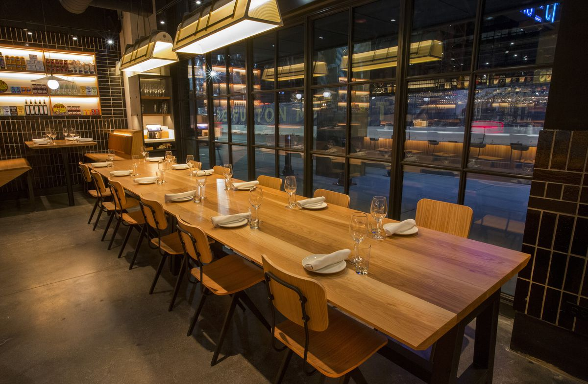A wooden rectangular table and seats with custom lights above.