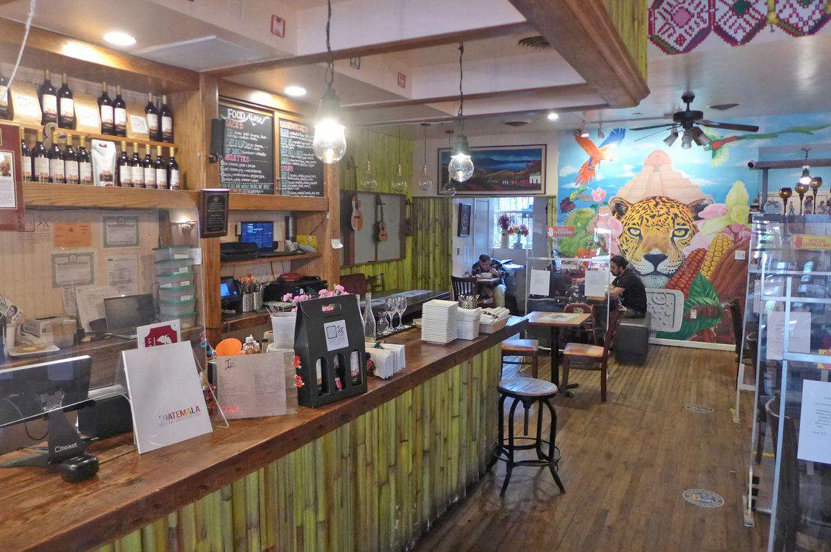 A bamboo bar on the left, and painting of a jaguar face straight ahead.