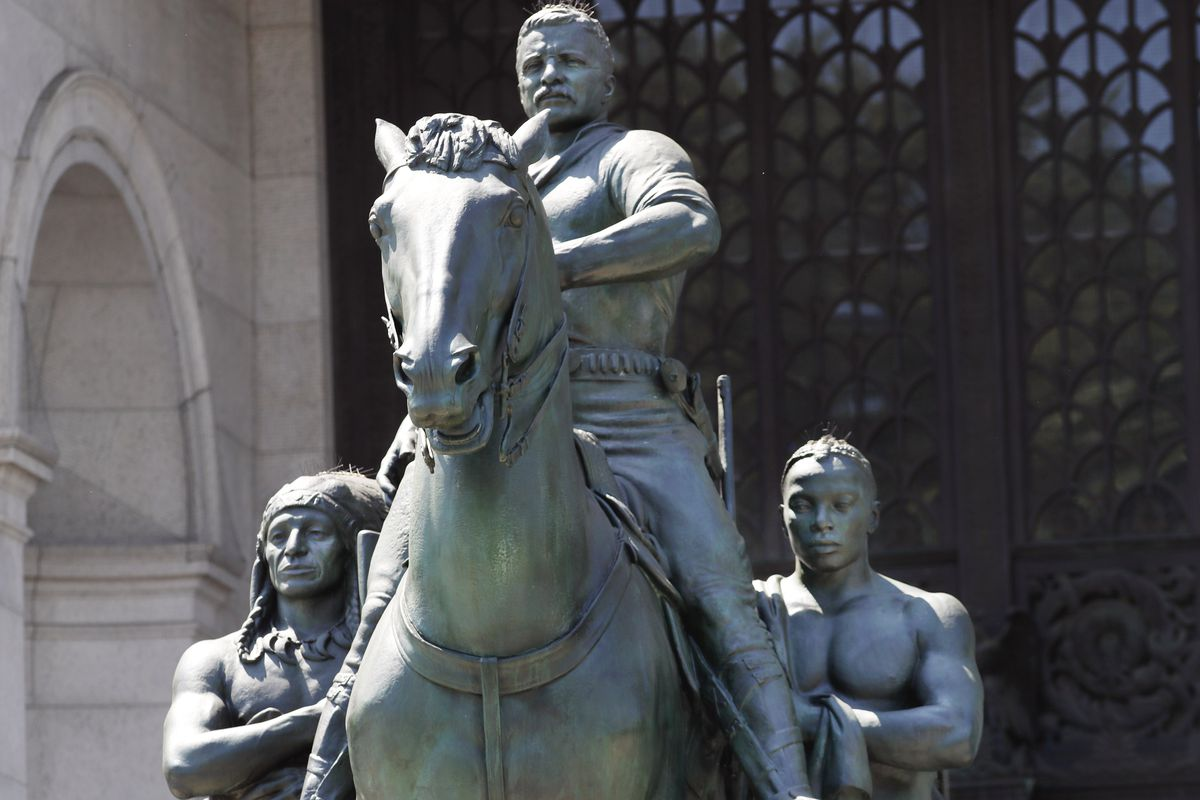 A statue of Theodore Roosevelt on horseback guided by a Native American man (left) and an African man, sits in front of the American Museum of Natural History, in New York.