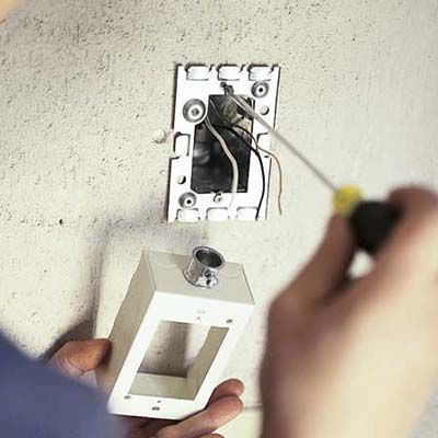 Man Attaches the Extension Box For Installing Outdoor Garage Lights
