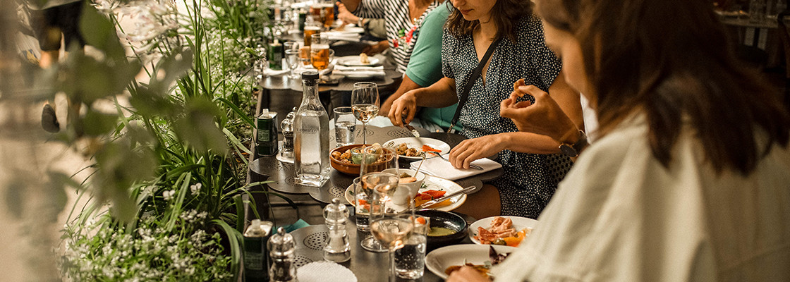 A long table where diners eat small plates and enjoy wine beside a long planter