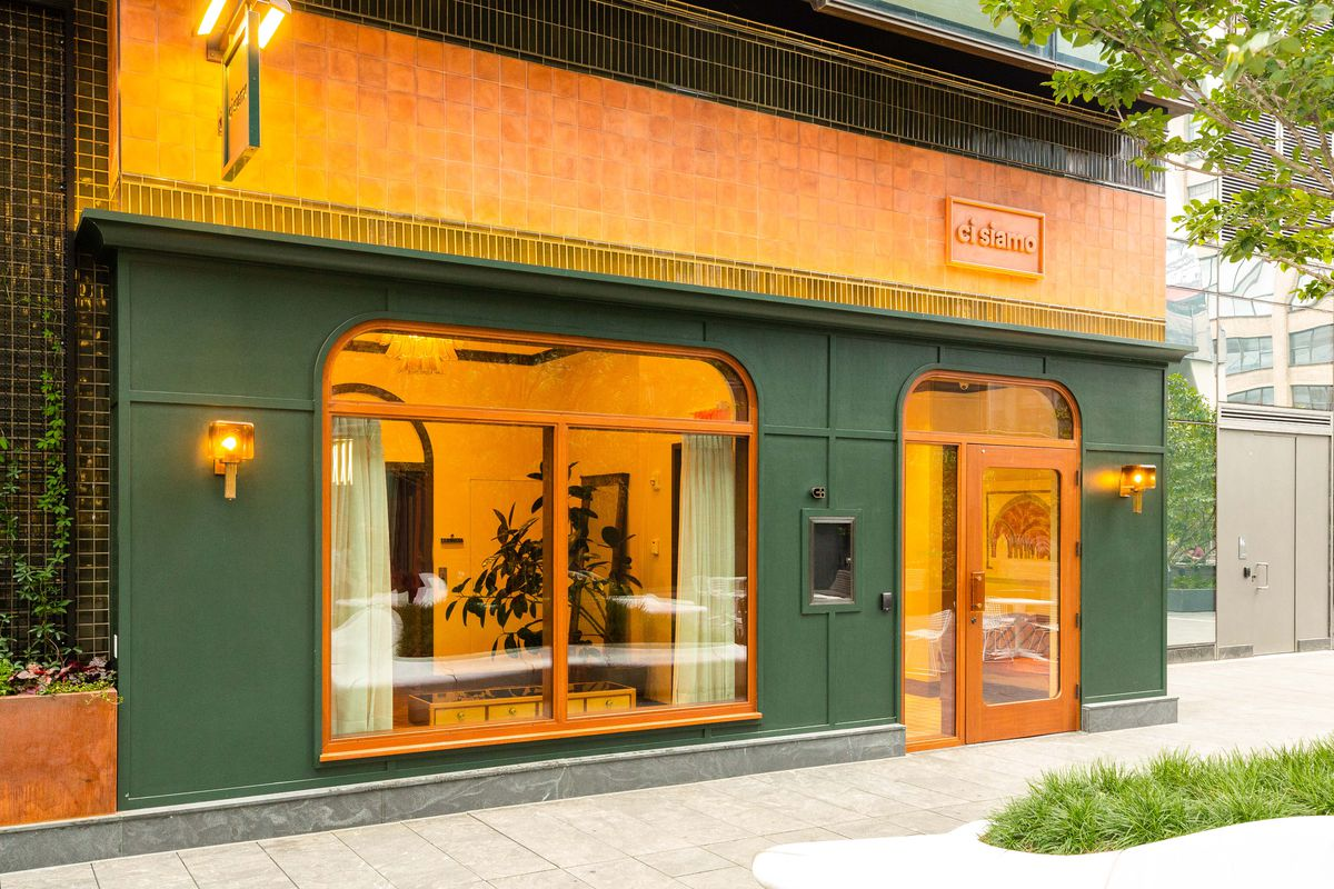 An exterior of a restaurant washed in dark green and firey orange and yellow tones.