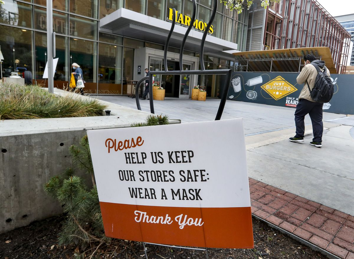 Signs remind customers to wear a mask while shopping at the Harmons grocery store in downtown Salt Lake City on Tuesday, April 6, 2021.