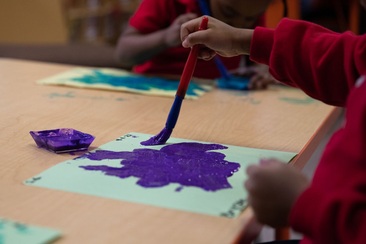 Two preschoolers paint with brushes in purple and turquoise on paper at a desk.