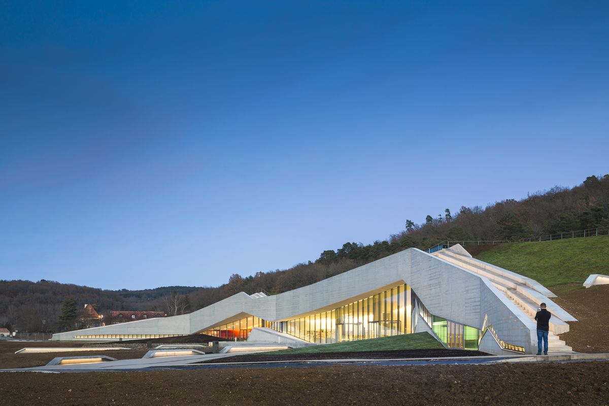 A low, long concrete building is built into the side of a hill, its roof line echoing the site's undulations with jagged points. Much of the facade is glazed.