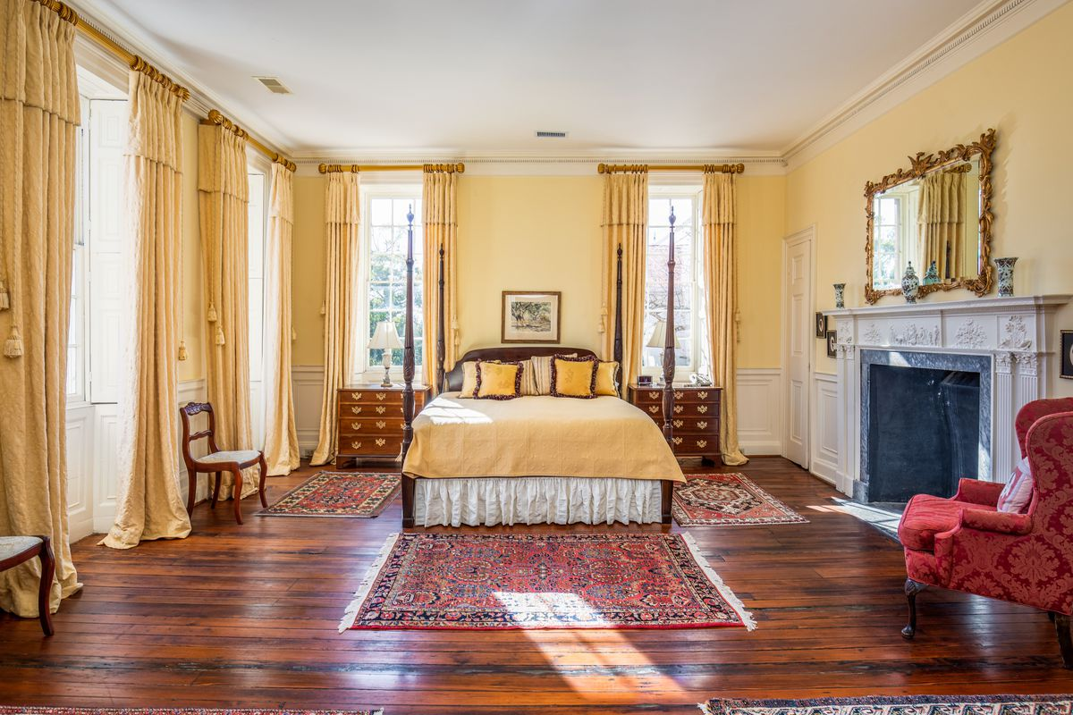 A master bedroom with wood floors, a yellow four-poster bed, and a fireplace.