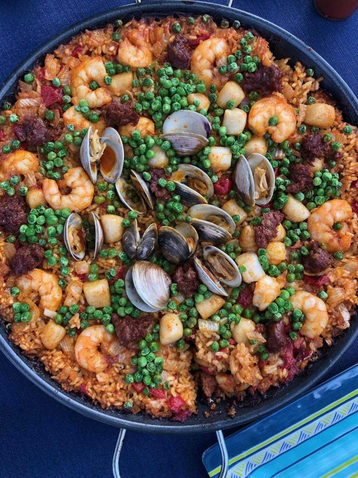 A pan of paella with peas and shellfish