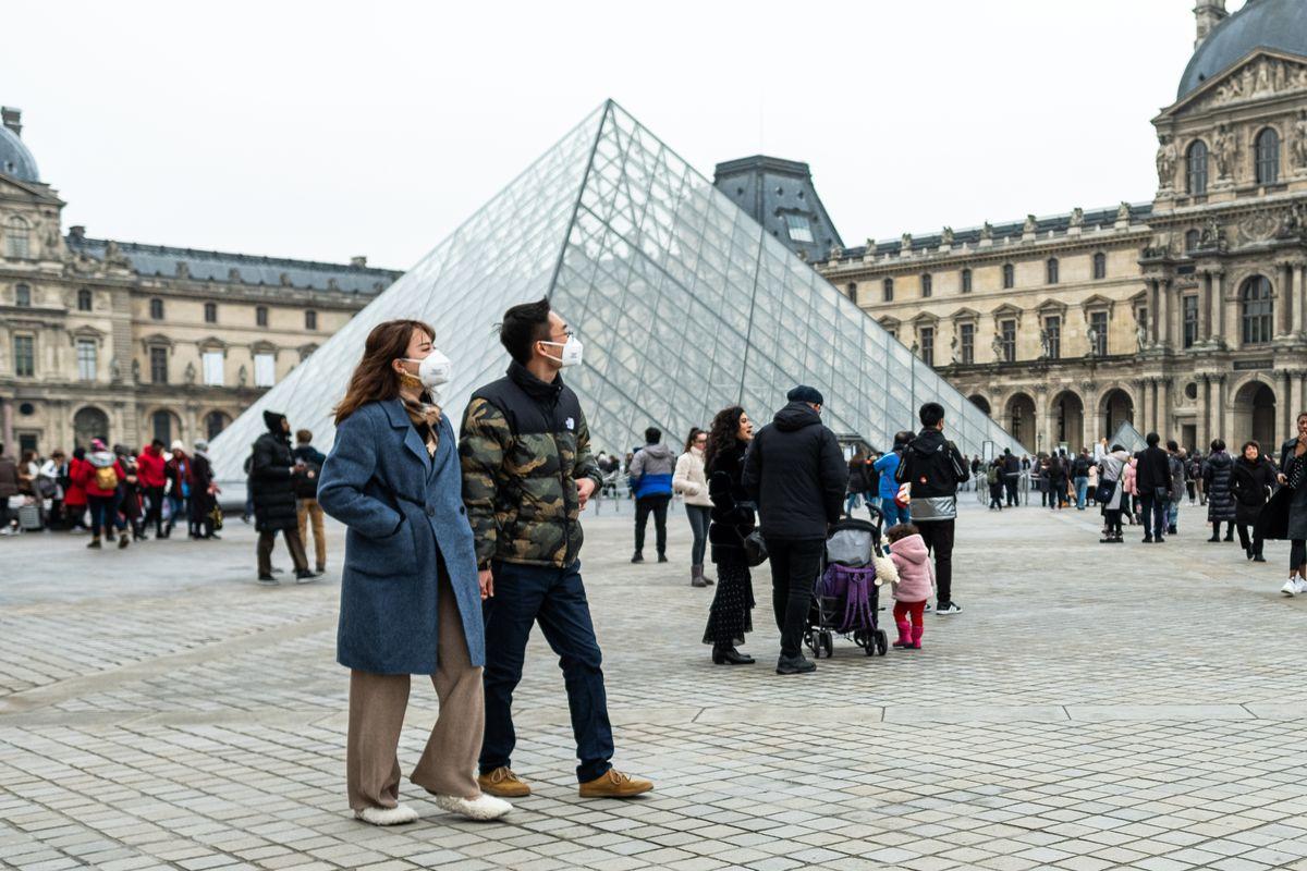 Tourists in Paris wear masks in response to coronavirus.