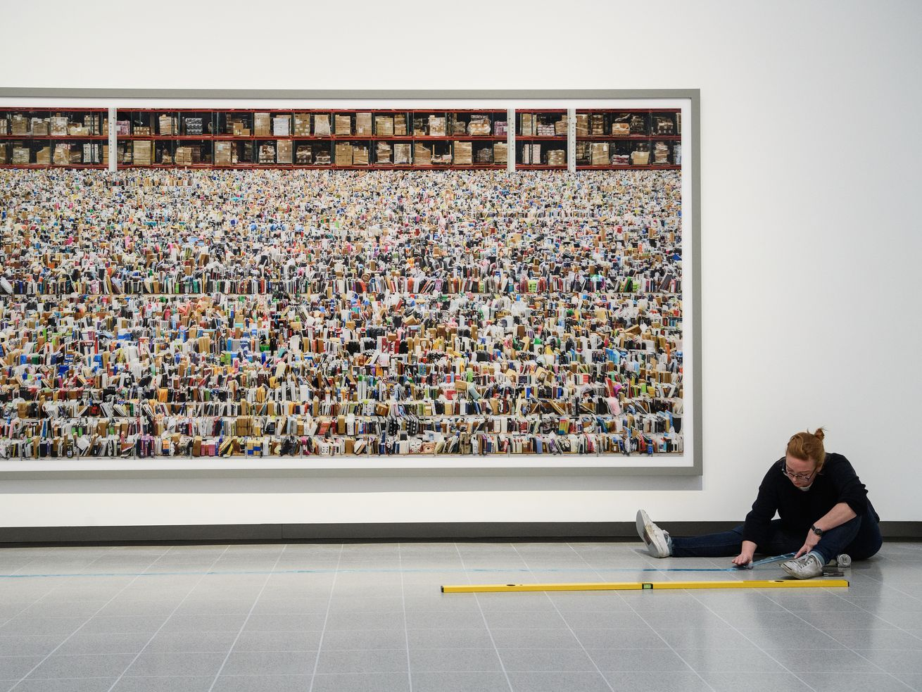 "A gallery assistant makes final preparations to a floor marker as she sits in front of the large-scale photograph ""Amazon"" by artist Andreas Gursky in the reopened Hayward Gallery on January 24, 2018, in London, England."